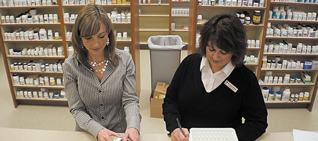 Holly Sebree, left, pharmacist, and Michelle Meyer, pharmacy technician, fill an order during the opening day of the new Medicine Store in Basehor.