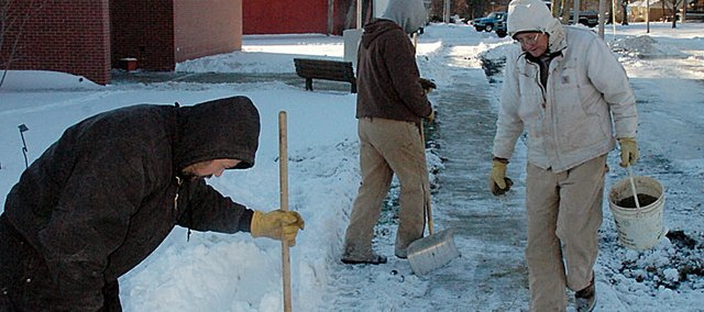 City workers remove snow and ice from the sidewalk in front of the Baldwin City Public Library last winter. This year, city administrators are asking downtown business owners to not use salt on the new sidewalks.