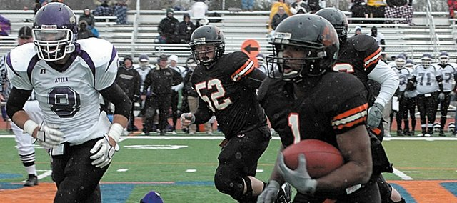 Baker University senior Richie Bryant, right, find an open area of turf to run after breaking through several Avila defenders during the first half of Saturday's contest. Bryant scored three touchdowns to help Baker win 43-9. Baker will play Morningside College in the national playoffs at 1 p.m. Saturday in Sioux City, Iowa.