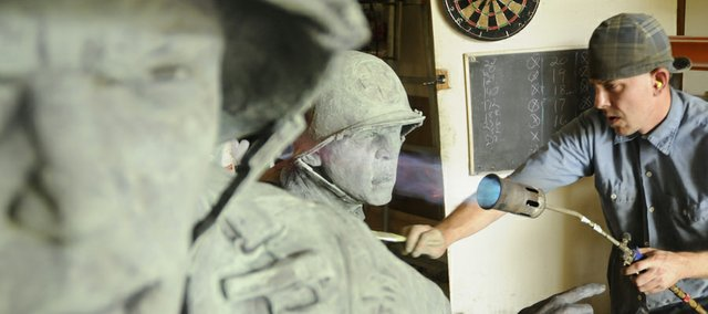 """Alan Austin applies a patina to the bronze sculpture """"Medic"""" last month in Lawrence. The sculpture, depicting a soldier flanked by a medic, is the most recent in a series of bronze sculptures by Lawrence artist Jim Brothers to be placed at the National D-Day Memorial in Bedford, Va."""