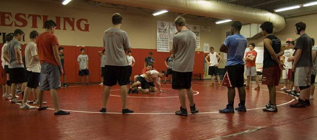 The Tonganoxie High wrestling team encircles coach Jeremy Goebel during a demonstration at practice.