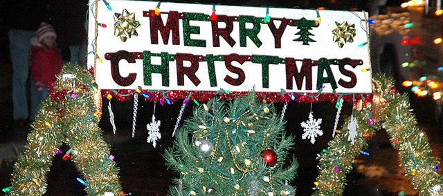 Baldwin City will kick off the season with its 10th annual Holiday Light Parade at 6 p.m. Saturday downtown. Here a Christmas sign was being pulled by two dogs in last year's parade.