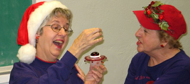 Rosemary Wasserman, left, exclaims at the holiday ornament she unwrapped during a Lansing Red Hat Movers and Shakers' Christmas party. Also admiring the ornament is Laura Barnes. Advocates for the elderly are urging senior citizens to put reassessment of their Medicare Part D insurance on their 2008 holiday shopping list.
