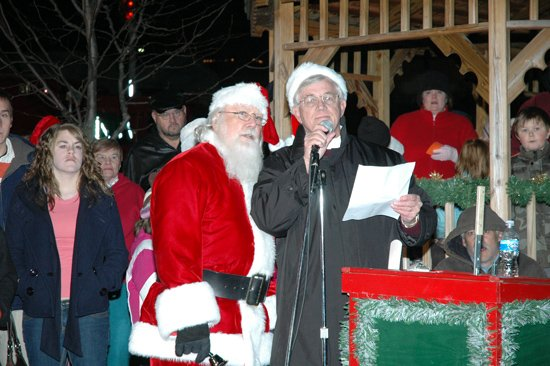 Bonner Springs Mayor Clausie Smith, right, gets a hand from Santa Claus in lighting the Mayor&#39;s Christmas Tree.