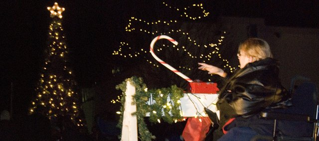 Mike Vestal, Tonganoxie mayor, pulls back after he used the candy cane switch to turn on the Mayor's Christmas Tree. This was the second year the annual tree-lighting ceremony took place downtown.