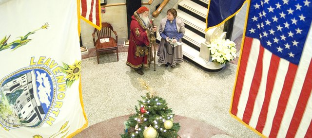 Tom Hooper, who is playing Father Christmas, speaks with Laura Elkins, who is playing Carrie Hall, a Leavenworth seamstress, during Friday's Christmas Open House at the Leavenworth County Courthouse. County employees and residents took on these roles to teach guests about the county's history.