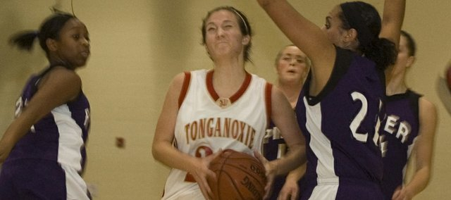 Chrissie Jeannin splits a pair of defenders on her way to the basket during Tonganoxie High's 45-38 defeat of Piper in the third-place game of the Cardinal Invitational on Thursday at Eudora.