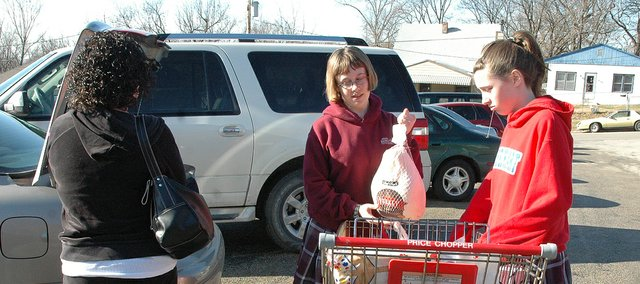 Susan Dietrich, middle, and Riley Cashion, right, of Sacred Heart push a shopping cart full of food.