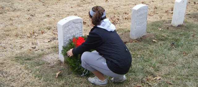 Fifth-grade student Claudia Jacobs places a holiday wreath on the grave of a fallen soldier Dec. 13, 2008 in Leavenworth National Cemetery.