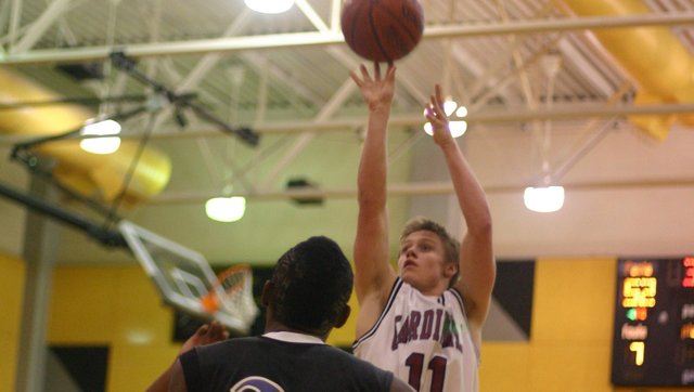 Evan Cleveland puts up a shot against K.C. Harmon in the championship game Friday at the Paola Invitational tournament. The Cardinals lost 76-59 and finished the tournament in second-place.  