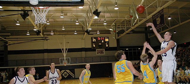 Baldwin High School senior Clad Kueffer, right, attempts a shot over a Central Heights defender during the second quarter of Friday&#39;s contest. Kueffer scored 11 points to help BHS beat the Vikings 52-31.