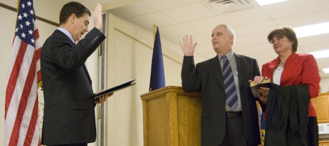 Michael Gibbens stands next to his wife, Nancy, as he is sworn into the position of First District Court judge by District Chief Judge David King on Friday. Gibbens was named to fill the position left by retiring judge Philip Lacey.  Gibbens chose the Tonganoxie Veterans of Foreign Wars Hall for the ceremony.