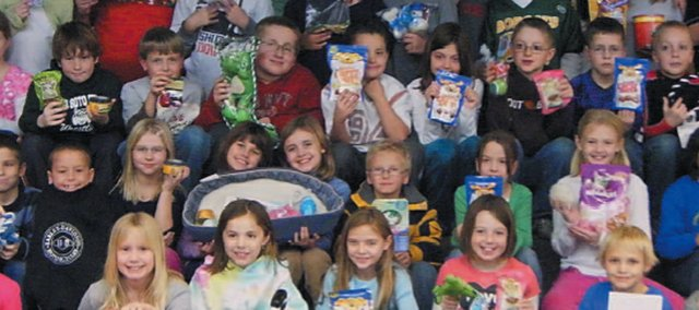 Third-Graders at Glenwood Ridge Elementary pose with items to be donated to Wayside Waifs animal shelter. The classes organized a charity drive called Caring for our Critters as part of a school project.