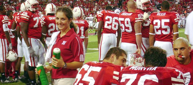 Laura Mertz, left, smiles after giving water bottles to members of the Nebraska football team. Mertz, a student athletic trainer for the Cornhuskers, will be working on the sidelines during the Gator Bowl on Thursday, Jan. 1.