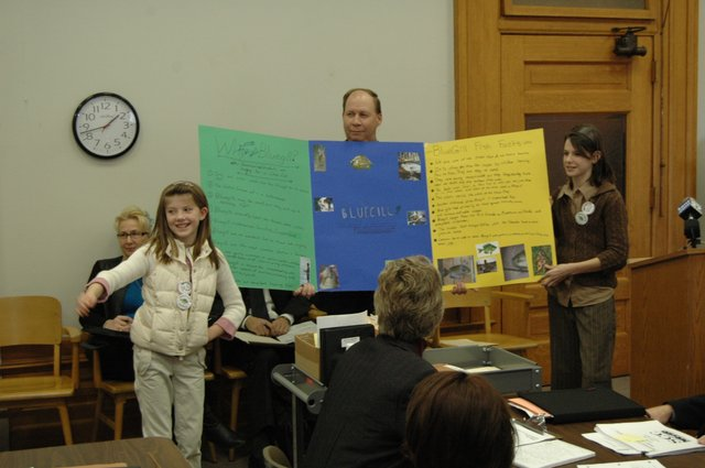 Tonganoxie Elementary School students Tressa Walker, left, and Sarah Ahart, right, get help from State Rep. Kenny Wilk, R-Lansing, while trying to convince members of a House committee that the bluegill should be Kansas' official state fish. In January, the students visited the capitol in Topeka to testify.