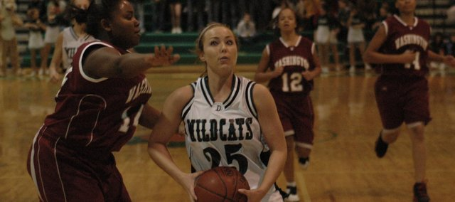 Kelsey Fisher drives in for a score against Washington Wednesday night at De Soto. Fisher scored eight points and hit two-three pointers in De Soto's 61-38 win.