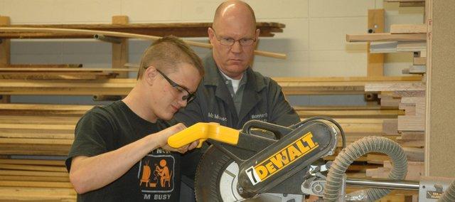 Kris Munsch, a teacher at Bonner Springs High School, helps Brent Tiner cut a piece of wood Tuesday during his advanced woods class.
