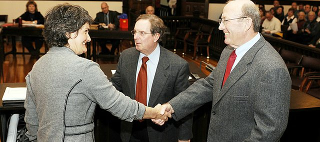 New county commissioners Nancy Thellman, left, and Jim Flory, right, shakes hands after being sworn in on Monday in the County Courthouse by Douglas County Chief Judge Robert Fairchild, center.