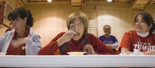 Denise LaRosh takes a big bite of her mystery food while Christine Biel anxiously waits for her turn and Suzanne Rucker, left, tries to keep her meal down. Twelve THS faculty and staff members participated in the Fear-Factor-like competition as part of an awards assembly Friday.