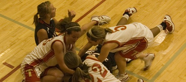 Chrissie Jeannin, Danielle Miller and Andie Jeannin of Tonganoxie go after a loose ball against Lansing on Friday. The Chieftains lost the Tonganoxie Invitational game, 54-39.
