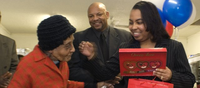Ann Jarrett, 100, left, hugs LaShawan Childs after getting a box of chocolates from LaShawan and Rev. Carlester Childs.