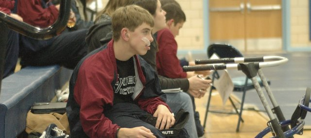 Eudora freshman wrestler Zach Herries waits by his walker before a freshman tournament at West Junior High in Lawrence. Herries has cerebral palsy and has limited movement in his lower body. He also uses hearing aids but must take them out before each match.