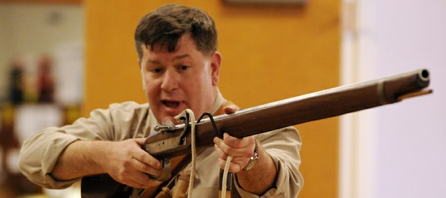 Shawn Faulkner, a military history professor at Fort Leavenworth, holds a rifle during a presentation at Kansas University's Military Science building. Faulkner offered historical tidbits about weapons to about 100 KU ROTC cadets, instructors and others on Thursday.