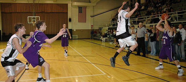 Baldwin High School senior Sam Beecher, right, sends a defender airborne while looking to the pass the ball inside to sophomore Justin Vander Tuig Tuesday night. Vander Tuig led the Bulldogs with 18 points as they beat Northern Heights 61-50.