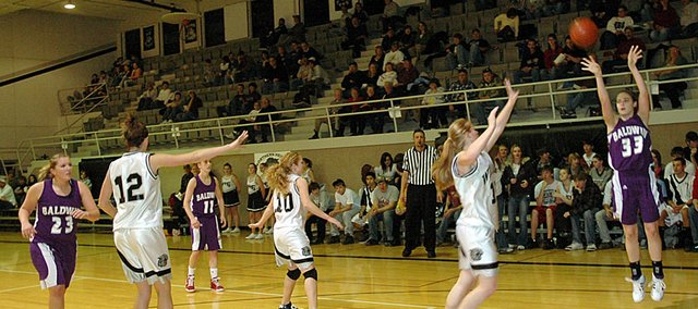 Baldwin High School senior Clare Miles, right, attempts a jump shot from the baseline Tuesday night during the Bulldogs&#39; 54-34 loss at Northern Heights.