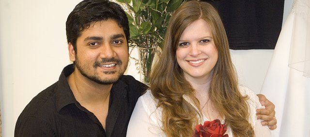 Laura and Ridhwi Mukerji were married Dec. 20 in Lawrence. The couple met through their parents, who are business associates. The couple had a Catholic wedding in Lawrence, but will have a Hindu-Bengali wedding in June in India. Pictured behind the Mukerjis are Laura's wedding dresses — the one behind her will be worn for the Indian ceremony; behind Ridhwi is the dress from the Dec. 20 wedding ceremony.