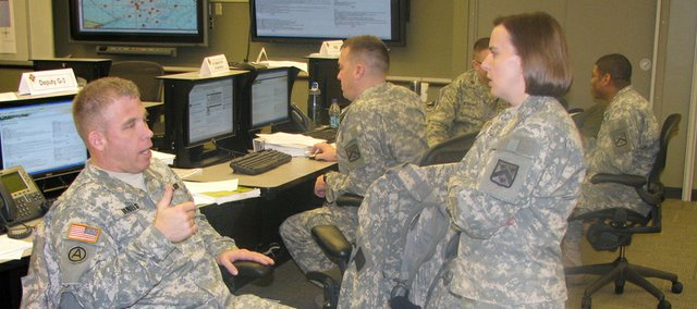Army Maj. Rachel Sullivan, right, a civil affairs officer, gets briefed on events occurring in a war game at Fort Leavenworth by Maj. David Daniels, left. More than 900 officers in the Command and General Staff College took part in the exercise, which spanned several days