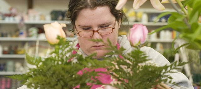 Michelle Docette makes a flower arrangement for Village Floral on Friday. Valentine's Day is the store's biggest sales day.