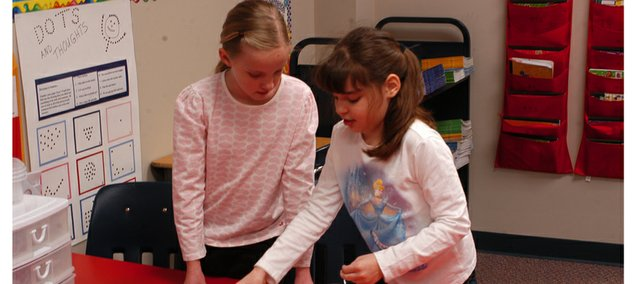 Starside third-graderAbigail Stutzman, left, helps Abby De with a card exercise Tuesday afternoon. Abby suffers from cerebral palsy and Abilgail has helped her during school since the girls were in kindergarten.