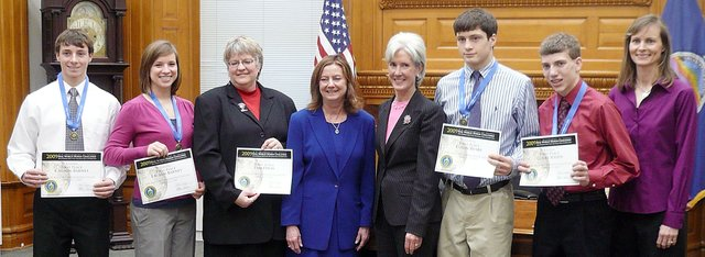 Four Baldwin High School students were honored Tuesday by Gov. Kathleen Sebelius for winning the first-ever U.S. Department of Energy's Real World Design Challenge. From left are Carson Barnes, Lauren Barnes, Pam Davis (coach), Commissioner of Education Alexa Posny, Gov. Sebelius, Colin Busby, Colby Soden and Sandy Barnes (coach). The students designed an airplane that improved fuel consumption. They met for many hours in the past several months to design the plane.