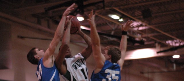 De Soto senior Jamel Townsend puts up a shot against two Gardner defenders Friday at De Soto. The De Soto boys led for most of the game, but Gardner outscored De Soto by 14 in the second half and won, 49-46.