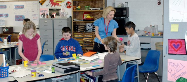 West Elementary School fourth-grade teacher Niki Rheuport works on an economics lesson with her students. Rheuport was named EWEs teacher of the year.