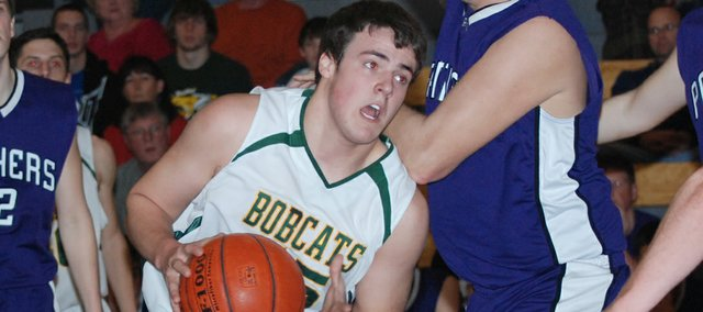 Basehor-Linwood junior Clint Schierbaum muscles his way past a Spring Hill defender during the first half of the Bobcats' 82-32 victory Monday in the first round of the Class 4A sub-state tournament.