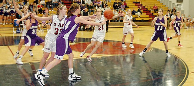 Baldwin High School sophomore Ramie Burkhart, left, throws a chest pass to senior Clare Miles (No. 33) during Tuesday's 49-46 sub-state loss at Saint James Academy.