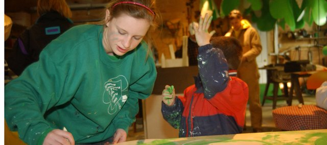Madison Fangman, 13, De Soto, paints a message that will be part of the O'Connor family float in the Kansas City St. Patrick's Day Parade, while her 6-year-old brother Max shows of his emerald green hand he painted while helping with the decorations. The family has a long history with the parade and hopes to repeat as the grand prize winner.