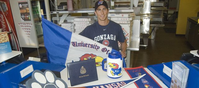 Patrick Kelly displays some of his Kansas and Gonzaga University collectibles. Kelly operates the Domino's Pizza in Tonganoxie.