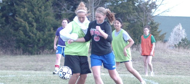 Kelsey Fisher and Tami Crow, right, battle for the ball during practice Monday at De Soto. De Soto opens the season at 4:30 p.m. Thursday at Spring Hill. The Wildcats lost to the Broncos last season and are looking to start this season with a win.
