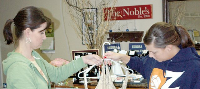 Erin Kracl, right, donates a prom dress to Heather Noble at Broers Flower Shop.