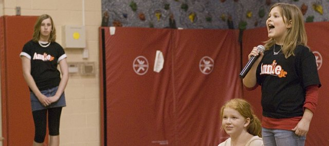 """On Friday, little orphan Annie, played by Emma DeMaranville, sings """"Tomorrow"""" along with her dog Sandy, played by McKinna Shelton.  DeMaranville, Shelton, Paige Lauri, who plays Lt. Ward, and other cast members from the Tonganoxie Middle School production of """"Annie Jr."""" performed for a group of fourth-graders at the Tonganoxie Elementary School and residents of the Tonganoxie Nursing Center. Also performing were Madison Derry, Dena Espeland, Halston Field, Lauren Harrell and Madison Tucker."""