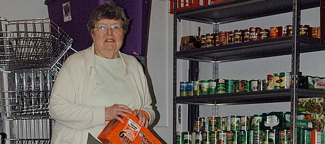 Ruth Dickinson, a volunteer with the Community Food Pantry, looks over the bounty of items that were collected Saturday morning by Boy Scout Troop 65.