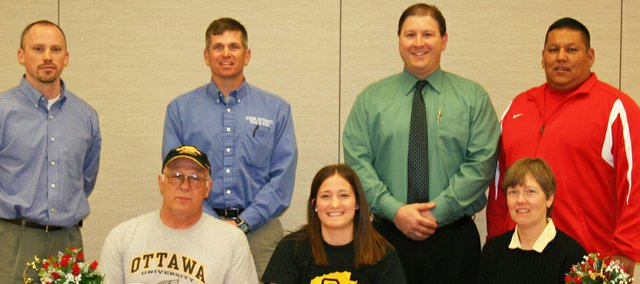 Chrissie Jeannin, center, signs on March 31 to play volleyball and throw javelin for Ottawa University. Seated next to Jeannin are her parents, Kenny and Wanda. Standing behind the Jeannins are Tonganoxie High volleyball coach Brandon Parker, Ottawa track coach Kirk Wren, Ottawa volleyball coach Tom Symons and Tonganoxie javelin coach Dave St. Cyr.