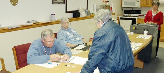 Election official Danny McMillen checks in a voter Tuesday morning at the Baldwin City Fire Station. As of 9 a.m., 41 people had cast votes there and the American Legion Hall. Douglas County Clerk Jamie Shew has upped his prediction of voter turnout here to 30 percent. He bases that partly on the city's advance voting turnout of 80 Saturday, which was the highest in the county.