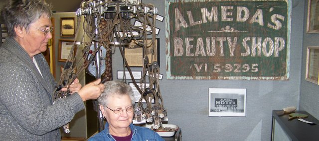 Lori Walters, McLouth, demonstrates using a permanent wave machine on Carol Slawson at the Tonganoxie Community Historic Site. The exhibit features items from the Almeda Beauty Shop, which operated in the 1940s and 1950s.