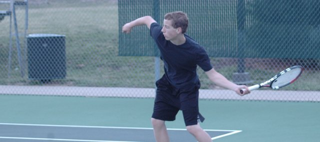 Trevor Elmer returns a serve at a recent De Soto tennis practice. Elmer and doubles partner Brendon Hudson, De Soto's No. 1 doubles team, went 2-1 Monday at the Topeka-Highland Park Quad. As a team, De Soto won 11 of 12 matches and took first-place at the event.