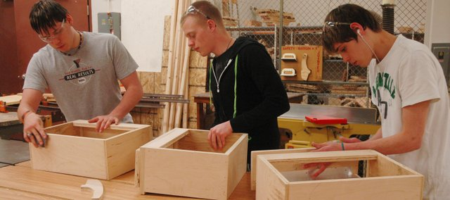 James Storms, left, Devin Dernovish, middle, and William Storms work on drawers that will be installed in the addition of the Bonner Springs High School concession stand. The BSHS woodworking students have been involved in building 60-feet of cabinets for the concession stand, saving the school district $22,000.