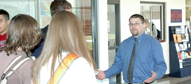 Eudora High School instructor Erik Peltzman talks with students Tuesday as they leave EHS. Peltzman was named the Eudora Chamber of Commerces Teacher of the Month for March.
